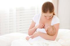 母亲在白色床上的哺乳新出生的婴孩