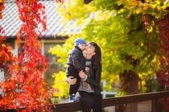 母亲在秋天公园拥抱她的儿子 免版税库存图片