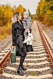 母亲在秋天森林中间拿着她的胳膊的儿子带着在火车轨道的一个手提箱 库存图片