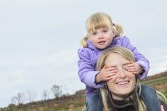 母亲在秋天的给女儿肩扛乘驾 免版税库存照片