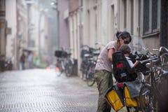 年轻母亲在自行车安置她的孩子在雨中 两栖 免版税库存图片