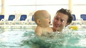 母亲在闭合的公共场所教她的婴孩游泳 孩子犹豫地荡桨手 孩子的发展,母亲的 股票录像
