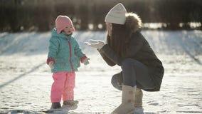 年轻母亲在雪在雪花在她的手上吹,小女儿看 有女婴使用的妇女 影视素材