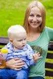 年轻母亲在他两岁的儿子的手上举行 库存图片