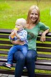 年轻母亲在他两岁的儿子的手上举行 库存照片