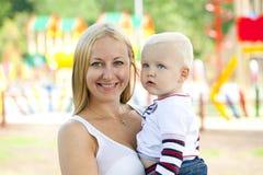 年轻母亲在他两岁的儿子的手上举行 免版税库存图片