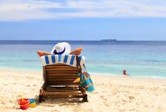 母亲在水中放松,当孩子戏剧在海滩时 免版税库存照片