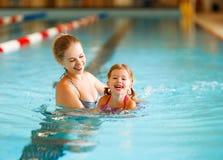 母亲在水池教孩子游泳 免版税库存照片