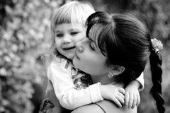 年轻母亲在绿色庭院里拥抱她的小女儿 免版税图库摄影
