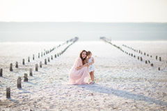 母亲女儿女孩妇女孩子坐沙子浪端的白色泡沫爱家庭 库存照片