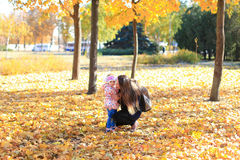 母亲女儿女孩妇女孩子坐爱家庭秋天黄色叶子树自然 免版税库存照片