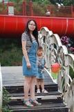 母亲妈妈举行她的女儿微笑笑获得乐趣享受时间在夏天公园愉快的儿童童年戏剧 库存照片