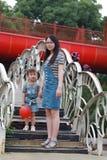 母亲妈妈举行她的女儿微笑笑获得乐趣享受时间在夏天公园愉快的儿童童年戏剧 免版税库存图片