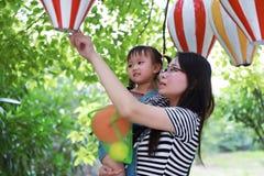 母亲妈妈容忍拥抱她的女儿笑获得乐趣享受业余时间在与气球的夏天公园愉快的儿童童年戏剧的微笑 库存照片