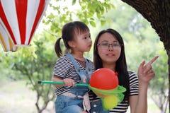 母亲妈妈容忍拥抱她的女儿笑获得乐趣享受业余时间在与气球的夏天公园愉快的儿童童年戏剧的微笑 免版税库存图片