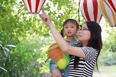 母亲妈妈容忍拥抱她的女儿笑获得乐趣享受业余时间在与气球的夏天公园愉快的儿童童年戏剧的微笑 库存图片
