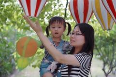 母亲妈妈容忍拥抱她的女儿笑获得乐趣享受业余时间在与气球的夏天公园愉快的儿童童年戏剧的微笑 图库摄影