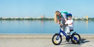 母亲学会他的小儿子骑自行车 免版税图库摄影