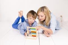 母亲学会计算与在一个白色地板上的儿子 库存照片