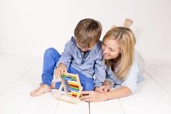母亲学会计算与在一个白色地板上的儿子 库存图片