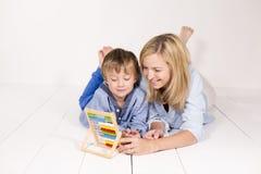 母亲学会计算与在一个白色地板上的儿子 免版税库存图片