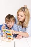 母亲学会计算与在一个白色地板上的儿子 免版税库存照片