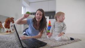 母亲孩子关系,有可爱宝宝男孩观看的动画片的愉快的妈妈在说谎手提电脑和拍手的手上  股票录像