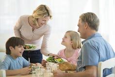 母亲对家庭的服务食物在表上 免版税图库摄影