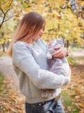 母亲小心地抱着一个俏丽的婴孩并且观看他 免版税图库摄影