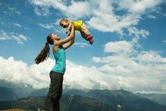 母亲带走她的胳膊的女儿 一个愉快的家庭的概念 日热夏天 水平的照片 免版税库存照片
