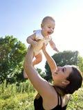 母亲带走她的胳膊的孩子 图库摄影