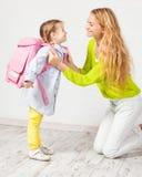 母亲帮助她的女儿准备好学校 库存照片