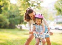 母亲帮助她的女儿学会骑自行车 图库摄影