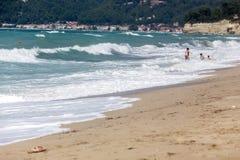母亲帮助她的孩子享用海滩 免版税库存图片