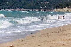 母亲帮助她的孩子享用海滩 库存照片