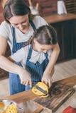 母亲帮助的女儿用胡椒 库存照片