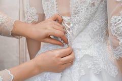 母亲帮助的新娘按礼服 图库摄影