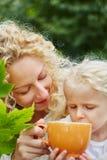 母亲帮助的daugther喝茶 图库摄影