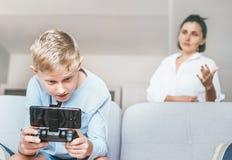 母亲怏怏不乐对于花费他的与el的时间的少年儿子 库存图片