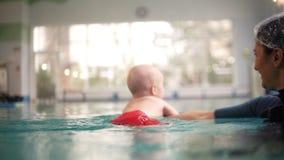 母亲或教练员在户内游泳场教男婴游泳,拿着他在水下 愉快的孩子享用 影视素材
