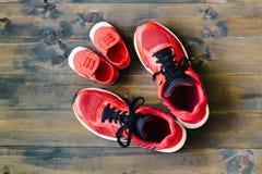 母亲或父亲两双红色体育跑鞋或运动鞋和 免版税库存照片