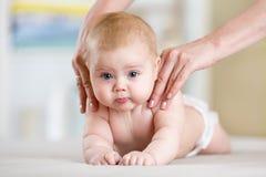 母亲或治疗师在家做按摩给她的婴孩 医疗保健和医学概念 免版税库存照片