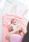 母亲投入了一些衣裳给她的婴孩 免版税库存照片
