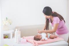 母亲投入了一些衣裳给她的婴孩 免版税图库摄影