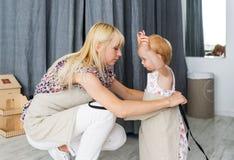 母亲投入围裙给小女儿 妈妈和女儿为清洗公寓做准备 库存照片