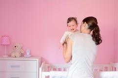 年轻母亲投入她的婴孩睡觉 库存照片