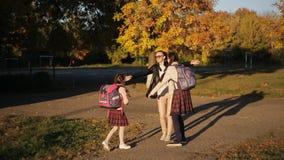 母亲护航他们的女儿对教学楼 妇女陪她的女儿去学校和挥动他们 影视素材