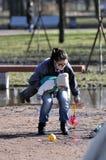 年轻母亲抱孩子,当尝试举玩具 免版税库存图片