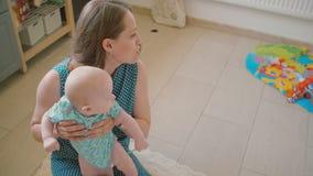 年轻母亲抱着她珍贵的婴孩并且对他微笑着坐厨房地板 慢的行动 股票录像