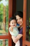 年轻母亲抱着她的站立和微笑对玻璃门的婴孩 库存图片